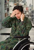 Close up of a handsome worry young soldier sitting on wheel chair using his cellphone, in a blurred background.  Stock Photos