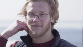 Close-up of handsome young blond man in glasses with blue eyes looking in the camera touching his hair. Attractive guy. Close-up of a handsome young blond man in stock video