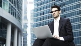 Close up of a handsome young businessman working with a laptop outside stock video
