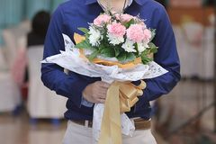 Close up of handsome young man holding beautiful bouquet of flower for his girlfriend. Sweet valentine`s day or wedding concept. Royalty Free Stock Image