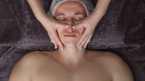 Close up of a handsome young man receiving facial massage at spa center.  stock images