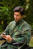 Close up of a handsome young soldier sitting on wheel chair using his cellphone in outdoors, in a backyard background.  Stock Images