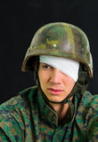 Close up of handsome young soldier wearing uniform suffering from stress, with a white bandage around his head and. Covering his eye, in a black background stock photos