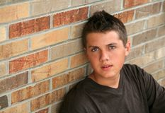 Close up of handsome young teen boy. Handsome young teen boy against brick wall Royalty Free Stock Image