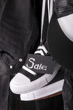 Close up of hanging black and white sneakers with sign Sale near jeans  cap on  background. Friday . Stock Images