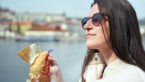 Close-up happy adorable woman enjoying ice cream dessert outdoor on embankment relaxing and smiling. Pleasant fashion tourist girl in sunglasses eating sundae stock footage