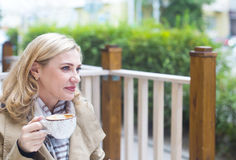 Close up happy adult blond woman with cup of coffee looking into Stock Photos