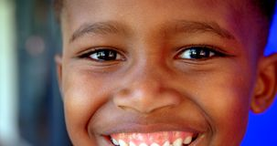 Close-up of happy African American schoolboy standing in school corridor 4k. Close-up of happy African American schoolboy standing in school corridor. He is stock footage