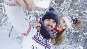 Close-up of happy attractive couple in the forest taking beautiful photos of themselves stock video