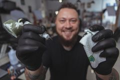 Expressive bearded tattoo artist working at his tattoo shop. Close up of a happy bearded tattoer smiling, reaching out to the camera holding tattoo machine royalty free stock image