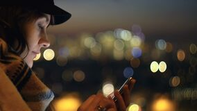 Close-up happy beautiful woman using smartphone at blurred night city background, her face is lit by screen slow motion.