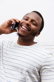 Close up happy black man laughing with cellphone Stock Photography