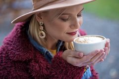 Pretty young woman smelling coffee with enjoyment Stock Image