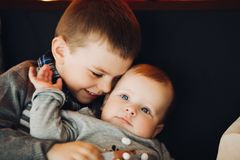 Happy boy embracing his little little brother. royalty free stock image