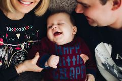 Happy boy smiling and playing together with parents. Close up of happy boy embracing his parents which looking each other. Lovely children wearing in royalty free stock image