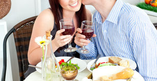 Close-up of a happy boyfriend kissing girlfriend. Close-up of a happy boyfriend kissing his beautiful girlfriend during dinner at home stock images