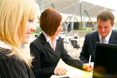 Close Up Happy Business Woman And Associates. Close up of blond woman with happy expression, background showing her two associates working together as a team Stock Photos