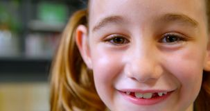 Close-up of happy Caucasian schoolgirl standing in library at school 4k. Close-up of happy Caucasian schoolgirl standing in library at school. She is looking at stock video