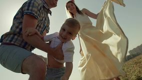 Close-up of happy child being thrown in the air several times. All the family enjoys the process stock video