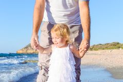 Close up happy child girl with her father holding hands and having fun walking on the beach. Family vacation, travel concept. Brig Royalty Free Stock Photo