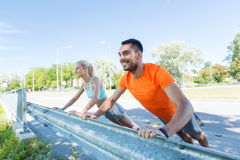 Close up of happy couple doing push-ups outdoors Stock Image
