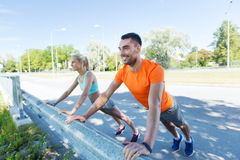 Close up of happy couple doing push-ups outdoors Stock Photo