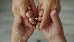 Close-up of happy couple holding hands, man is caressing woman's palms