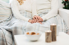 Close up of happy couple at home for christmas. Love, family, winter holidays and happiness concept - close up of happy couple sitting under plaid at home for Royalty Free Stock Photography