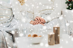Close up of happy couple at home for christmas. Love, family, winter holidays and happiness concept - close up of happy couple sitting under plaid at home for Stock Images