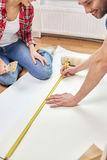 Close up of happy couple measuring wallpaper Stock Photography