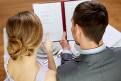 Close up of happy couple with menu at restaurant Royalty Free Stock Photos