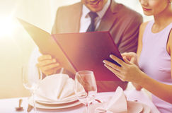Close up of happy couple with menu at restaurant Royalty Free Stock Photography