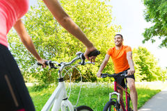 Close up of happy couple riding bicycle outdoors Royalty Free Stock Photo