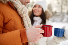 Close up of happy couple with tea cups in winter. People, winter, drinks and season concept - close up of happy couple holding hot tea cups Royalty Free Stock Photos