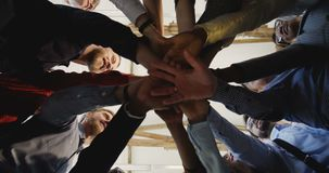 Close-up happy diverse adult business people joining hands together. Team spirit at modern multiethnic loft office.