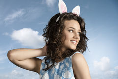 Close-up of happy easter girl. Close-up portrait of beautiful brunette girl with easter funny style, pink bunny ears and lovely spring dress Royalty Free Stock Photos