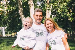 Close-up happy family in identical T-shirts with numbers and inscriptions - Family team, Mom, Dad - hugging in the park. Family day stock photos