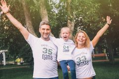 Close-up happy family in identical T-shirts with numbers and inscriptions - Family team, Mom, Dad - hugging in the park. Family day stock images