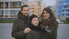 Close up of happy family in warm clothing are standing together on the street smiling and looking at camera. Father and stock video