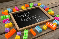 Close up of happy fathers day message on slate by toy blocks Royalty Free Stock Photos