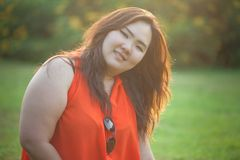 Close up of happy fatty woman. Close up of happy fatty asian woman outdoor in a park Royalty Free Stock Images
