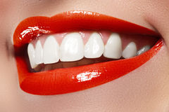 Close-up happy female smile with healthy white teeth, bright red lips make-up. Cosmetology, dentistry and beauty care. Macro of woman's smiling mouth Stock Image