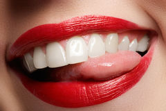 Close-up happy female smile with healthy white teeth, bright red lips make-up. Cosmetology, dentistry and beauty care. Macro of woman`s smiling mouth Stock Image