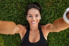 Close up of a happy fitness girl in earphones. Taking a selfie while laying on grass outdoors Stock Photos