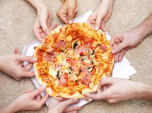 Close up of happy friends eating pizza at home Royalty Free Stock Photos