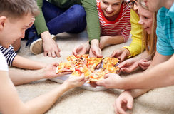Close up of happy friends eating pizza at home Stock Photography