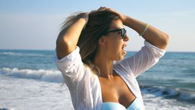 Close up of happy girl in bikini and shirt walking along coast and smiling. Young beautiful woman in sunglasses playing. With her blonde hair and enjoying stock video