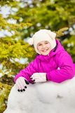 Close-up of happy girl stands behind the snow wall Royalty Free Stock Photo