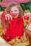 Close up of happy girl wearing a red dress and holding a christmas ball and decoration in her hands, with a Christmas. Tree behind, christmas concept Stock Photography