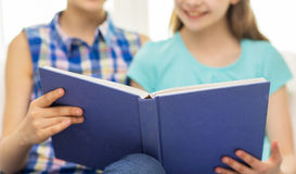 Close up of happy girls reading book at home Royalty Free Stock Photo